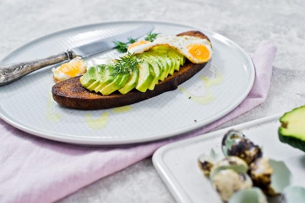 Avacado sandwich with egg on toast of black bread. Premium Photo