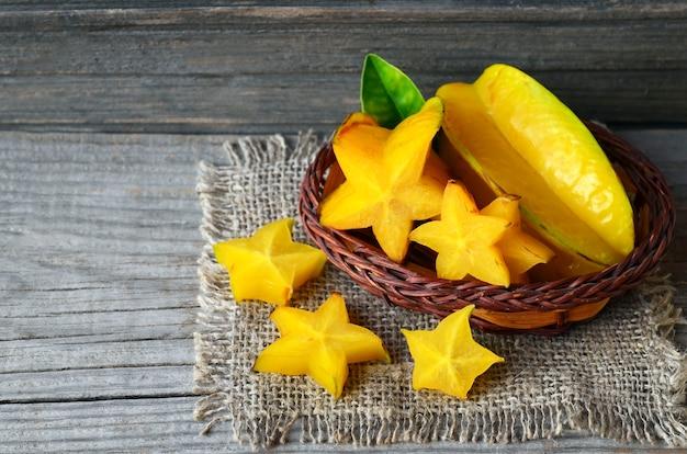 Тропический экзотический плодоовощ карамбола в маленькой корзине на старом деревянном столе. предпосылка карамболы старфрута или averrhoa. концепция здорового питания, вегетарианские или диета. Premium Фотографии