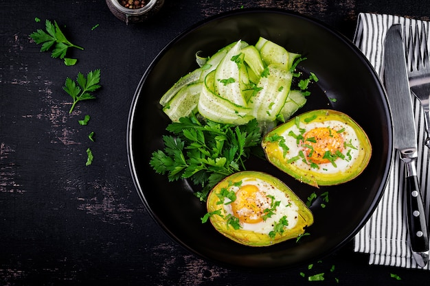 Avocado baked with egg and fresh salad. vegetarian dish. top view, overhead.  ketogenic diet. keto food Premium Photo