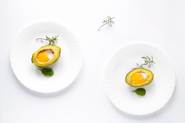 Avocado baked with egg in a plate over white background Free Photo