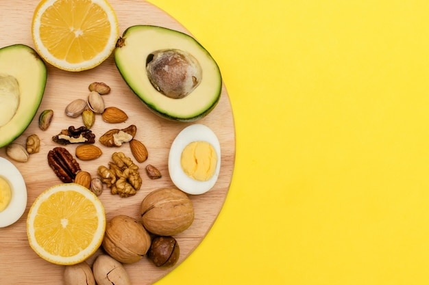 Avocado,eggs,lemon,nuts on the wooden cutting board. concept of healthy food.flat lay ketogenic diet. Premium Photo