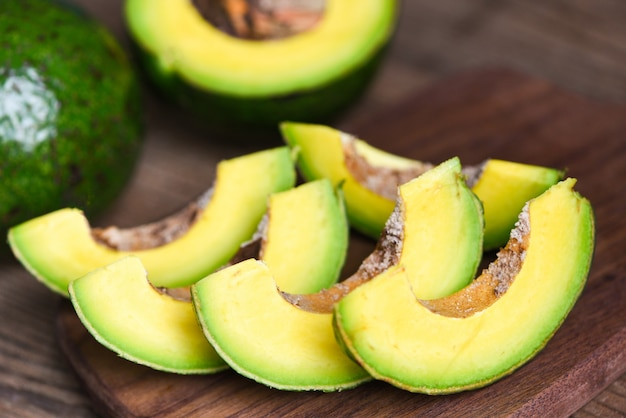 Фрукты авокадо и ломтик авокадо на деревянном Premium Фотографии