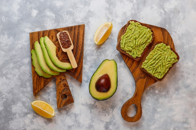 Avocado open toast with avocado slices, lemon, flax seeds, sesame seeds, black bread slices, top view Free Photo