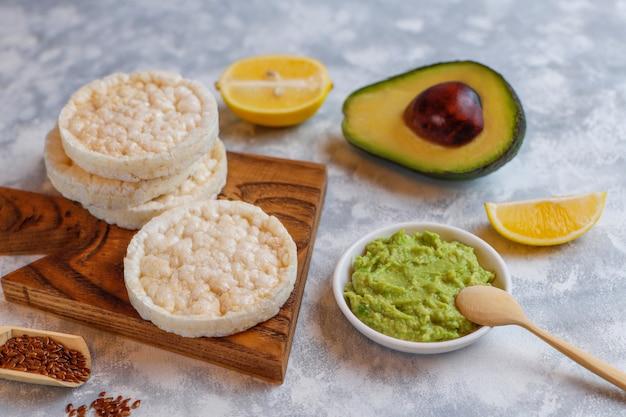 Avocado open toast with rice bread, lemon slice, avocado slices, seeds top view. Free Photo