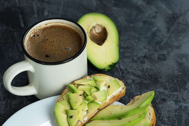 Avocado sandwiches breakfast and a cup of coffee Premium Photo