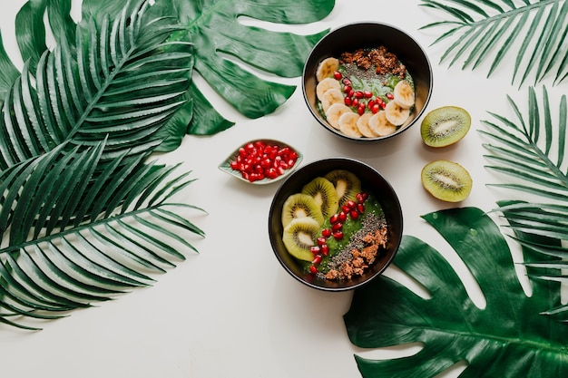 Чаша для смузи из авокадо с чиа, мюсли, киви и шпинатом. накладные, вид сверху, плоская планировка. здоровый завтрак. тропические листья. Бесплатные Фотографии