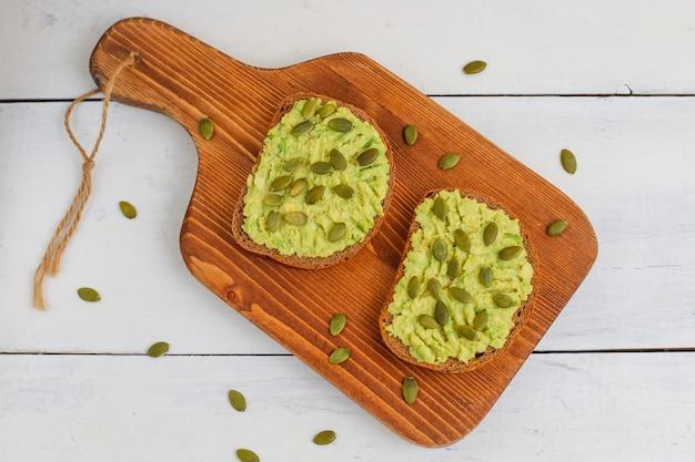 Тост из авокадо на цельнозерновом хлебе с овощами, желтыми и красными помидорами Бесплатные Фотографии