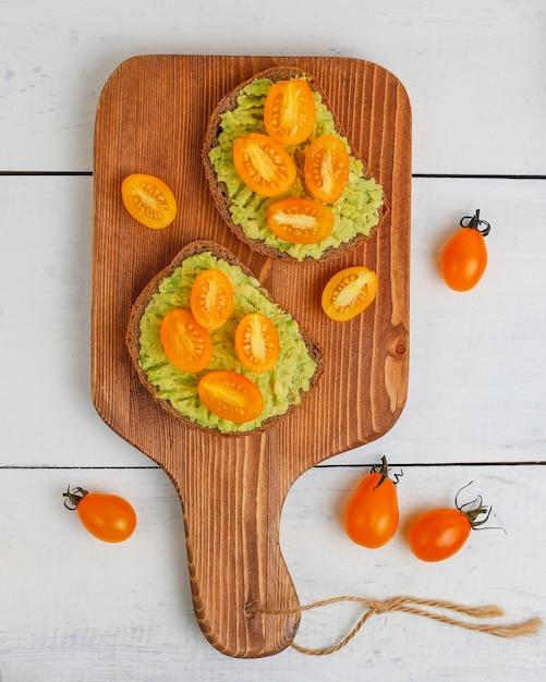 Тост из авокадо на цельнозерновом хлебе с овощами Бесплатные Фотографии