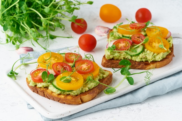 Avocado toast with cherry tomatoes and herbs, breakfast, closeup Premium Photo