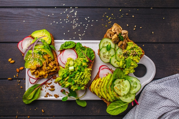Avocado toasts with different toppings, top view, dark wooden background.