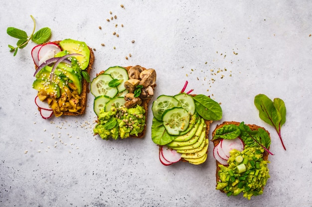 Avocado toasts with different toppings, top view, white background, copy space. Premium Photo
