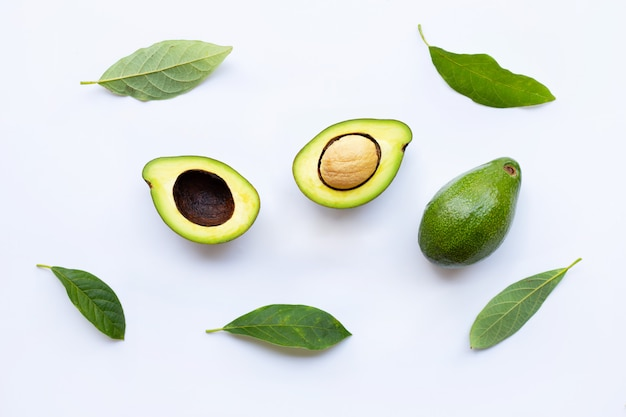 Avocado with green leaves on a white Premium Photo