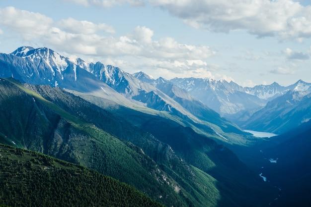 高山湖のある素晴らしい山々の氷河と緑の森の谷への素晴らしい空中写真 Premium写真