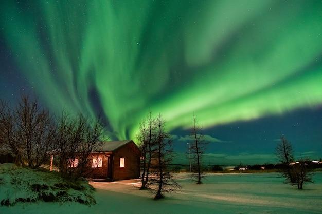 눈으로 덮인 아름다운 별장 위의 멋진 오로라 프리미엄 사진