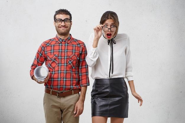 Uomo allegro goffo con espressione comica, detiene il progetto, si trova vicino alla femmina sorpresa scioccata Foto Gratuite