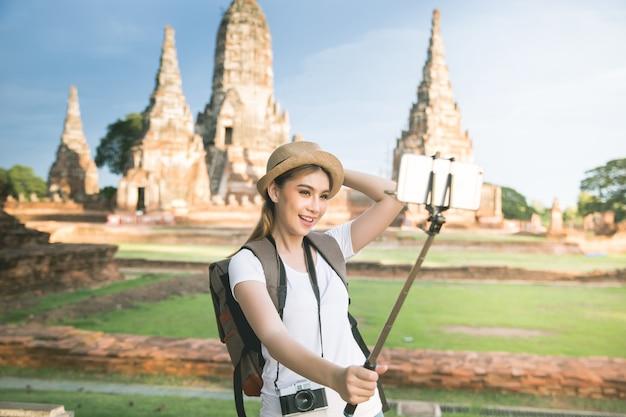 Молодой азиатский женский путешественник с рюкзаком путешествуя провинция ayutthaya, таиланд Бесплатные Фотографии