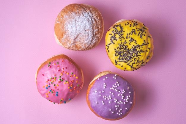 ピンクの紙の背景に色付きのaze薬で4つのドーナツ。 Premium写真