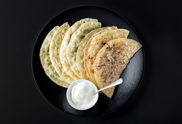 Azerbaijan national cuisine different kutabs with sauce on black plate. Premium Photo