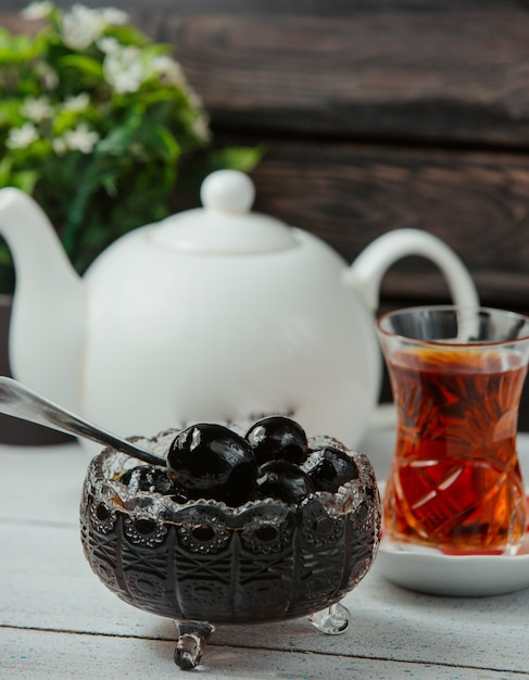 Azerbaijani walnut jam in crystal bowl served with black tea Free Photo