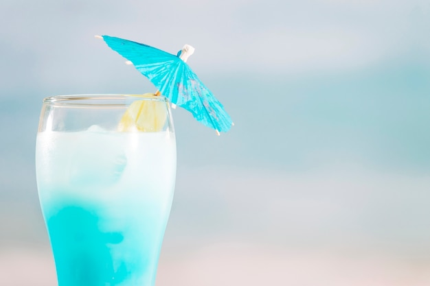Azure cocktail with umbrella in glass Free Photo