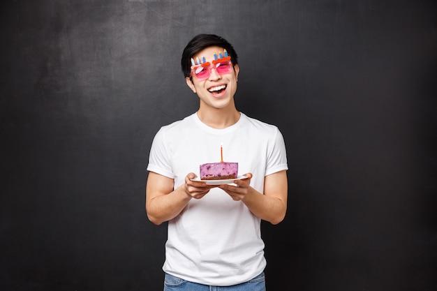 誕生日、お祝い、パーティーのコンセプトです。 bデーを祝う熱狂的なかわいいアジアの男、頭を傾け、喜んで笑顔で幸せなカメラを見る Premium写真