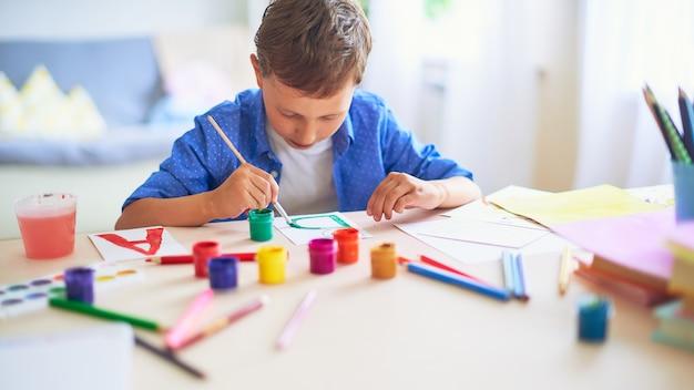 子供は、紙にブラシで水彩絵の具で描く文字b Premium写真