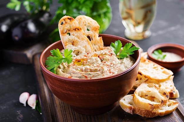 Baba ghanoush vegan hummus from eggplant with seasoning, parsley and toasts. baba ganoush. middle eastern cuisine. Premium Photo