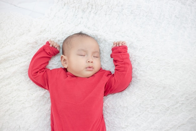Babies wearing red shirts sleeping in bed Free Photo
