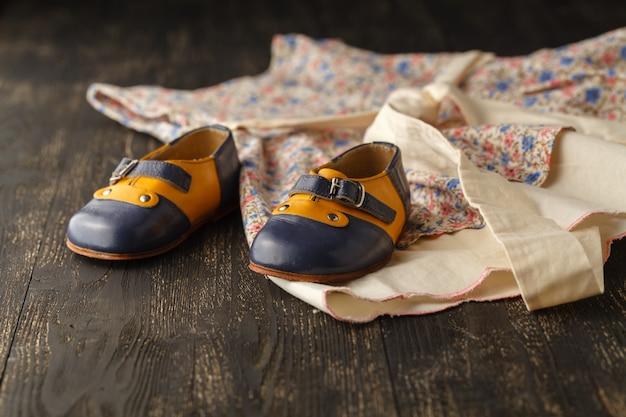 Стол для детских аксессуаров: легкое цветочное платье и обувь для девочки, стол с копией пространства Premium Фотографии