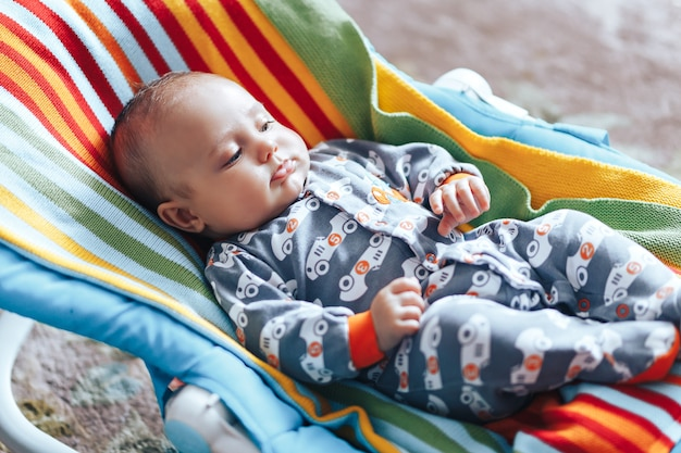 Baby in baby chaise deck-chair colourful home Premium Photo