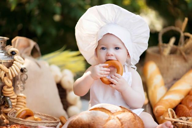 Малыш пекарь на пикнике ест хлеб и бублики в белом фартуке и шапке на природе в солнечный летний день Premium Фотографии