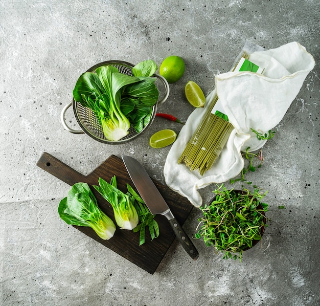 Baby bok choi halves, uncooked green tea noodles, limes, green sprouts on gray background. top view, square image Premium Photo