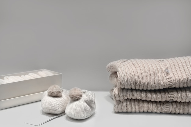 Baby booties, sweaters and socks made of natural beige fabrics lie on the table Premium Photo