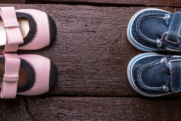 木製の背景に男の子と女の子の靴。子供の靴。上面図。 Premium写真