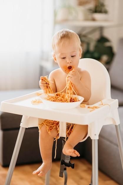 Neonato che mangia pasta nel suo seggiolone Foto Gratuite