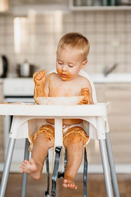 Neonato che mangia pasta con le sue mani Foto Gratuite