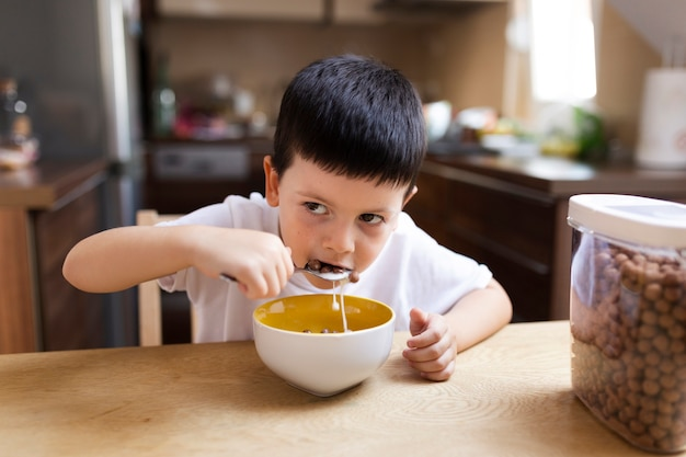 Baby boy having breakfast at home Free Photo