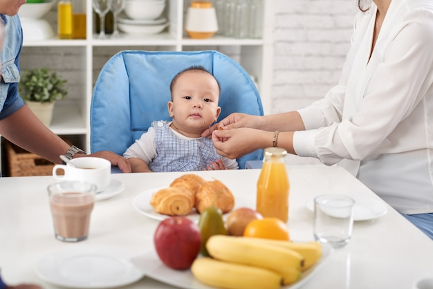 Baby boy joining family dinner Free Photo