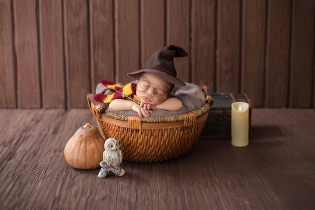 Baby boy laying inside little basket with funny wizard costume Free Photo