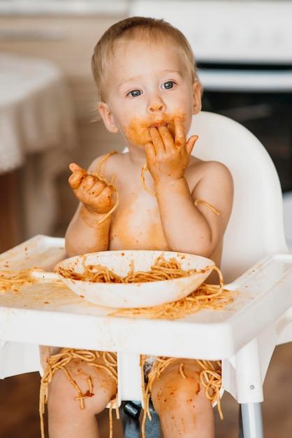 Neonato che si lecca le dita dopo aver mangiato la pasta Foto Gratuite