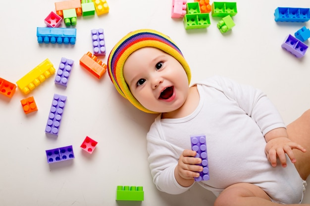 Baby boy playing with a multi-colored constructor on a white wall Premium Photo