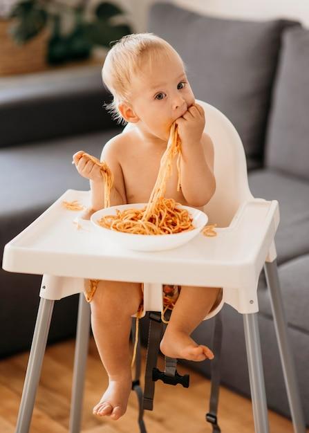 Neonato che gioca con la pasta nel suo seggiolone Foto Gratuite