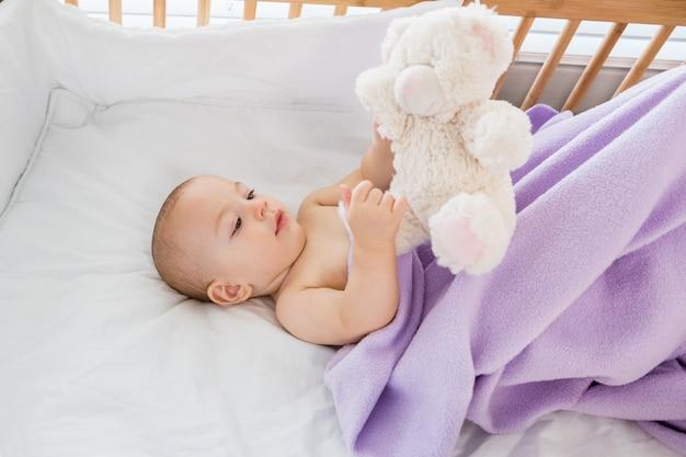 Neonato che gioca con un giocattolo morbido su una culla Foto Gratuite