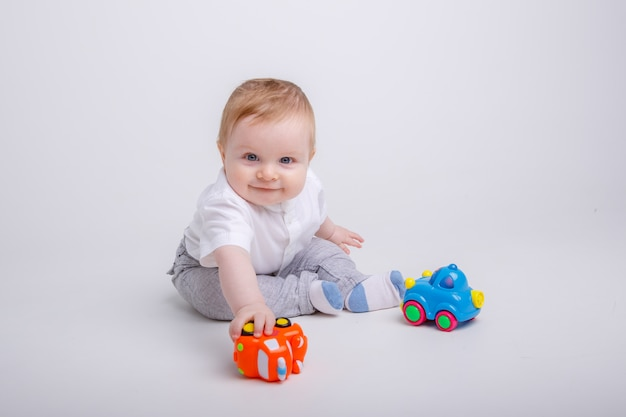 Baby  boy playing with toy cars on white background Premium Photo