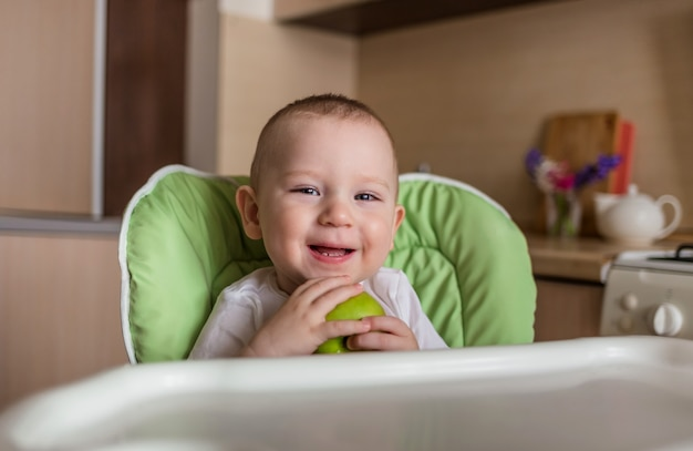 Baby boy sits in a chair and eats green apple Premium Photo