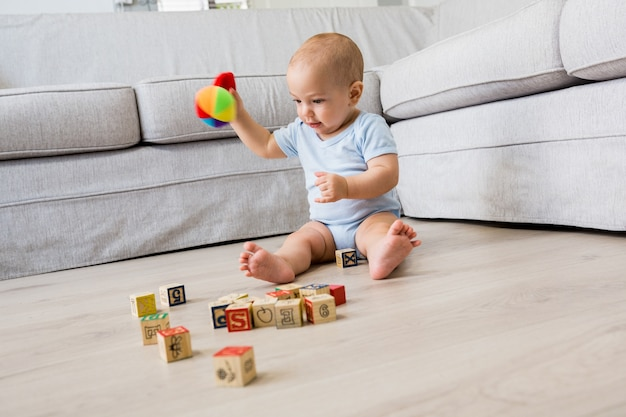 Baby boy sitting on floor and playing with toys in living room Free Photo