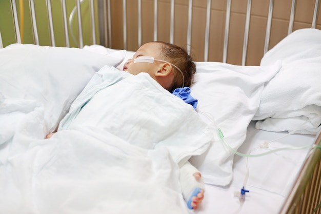 Baby boy with breathing tube in nose receiving medical treatment. Premium Photo