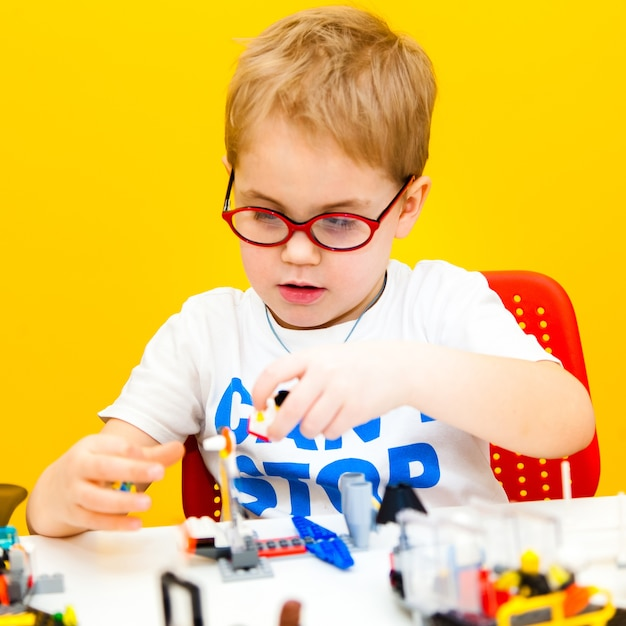 Baby boy with glasses playing with lego construction toy blocks at home Premium Photo