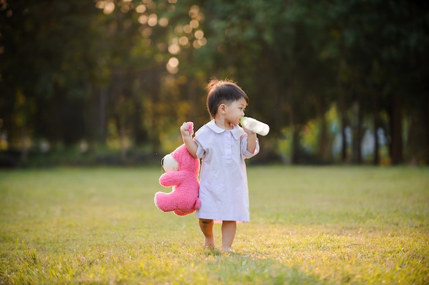Baby child relaxing in garden and drinking milk from bottle. Premium Photo
