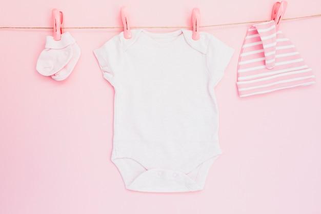 Одежда для младенцев, висящая на розовом Бесплатные Фотографии
